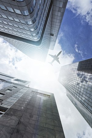 plane flying over a modern glass and steeel office towers in Frankfurt am Main, Germany photo