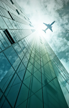plane flying over a modern glass and steel office building in Frankfurt am Main, Germany