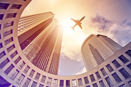plane flying over modern office tower in the sun, Frankfurt am Main, Germany