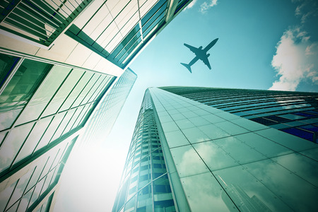 corporate jet: plane flying over a modern glass and steeel office towers in Frankfurt am Main, Germany Stock Photo