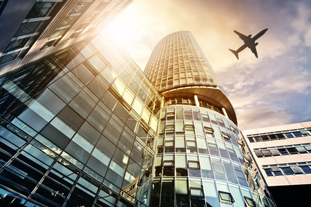 plane flying over highrise office buildings seen from below Stockfoto