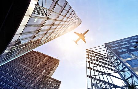 Vliegtuig dat over moderne glas en staal kantoorgebouwen in de buurt van de Potsdamer Platz, Berlijn, Duitsland