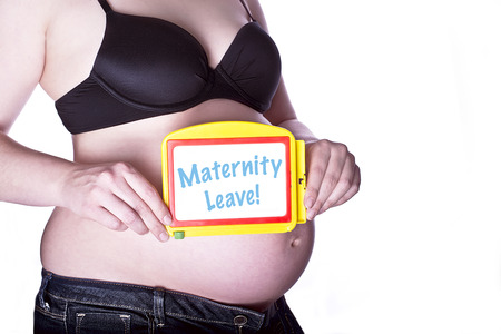 maternity leave: pregnant woman clothed in black bra and jeans holding a toy slate with text Maternity Leave in front of her belly