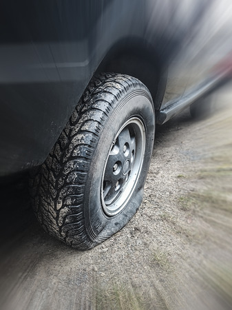 flat tire: flat tire of a vehicle, intentional blur