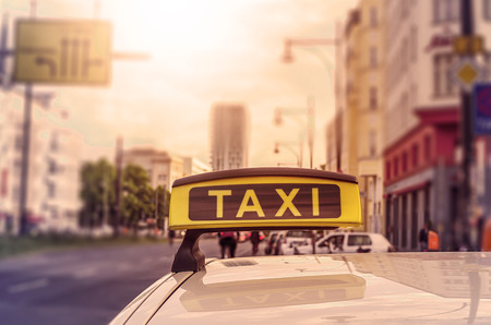 taxi sign: Taxi sign on top of a german cab in the evening sun, intentional selective focus Stock Photo