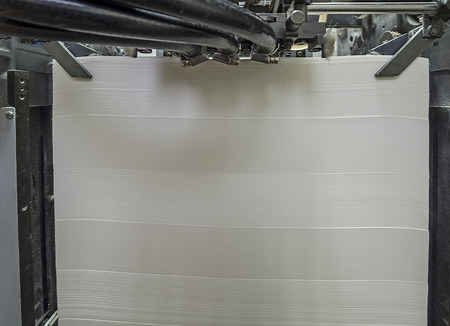 offset printing: Stack of blank paper in a modern offset printing machine Stock Photo