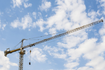 yellow construction crane in front of a cloudy sky used for heavy lifting