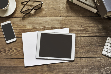 desktop: blank tablet and phone placed on an wooden desktop workspace Stock Photo