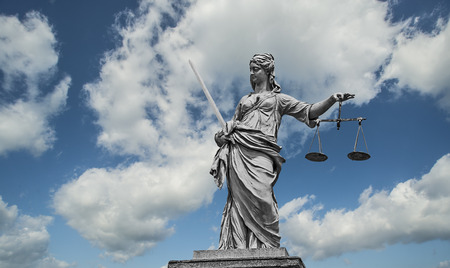grey scale: Statue of Lady Justice holding scales and sword in front of a blue cloudy sky