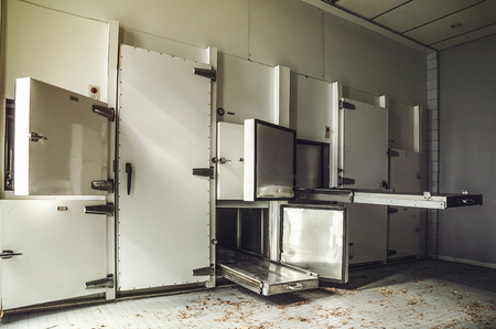 old morgue with steel trays and body fridge in an abandoned hospital complex