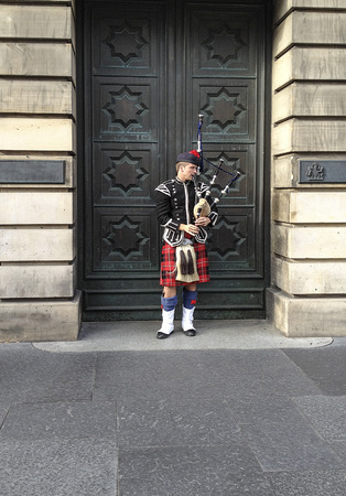 bagpipe: EDINBURGH, SCOTLAND - SEPTEMBER 15, 2012: Bagpipe player with traditional scottish clothing playing in front of a huge door Editorial