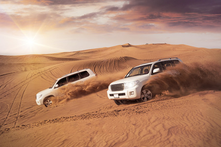 dwa pojazdy 4x4 walnąć się na boki przez wydmy pustyni w wieczornym słońcu