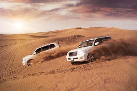 twee 4x4 voertuigen bashing links naar rechts door de woestijn duinen in de avondzon