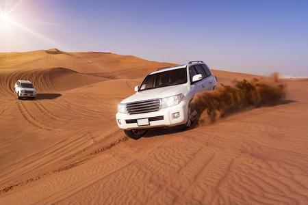Todo terrenos desérticos que golpean a través de las dunas de arena árabe Foto de archivo