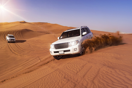 desierto del sahara: Todo terrenos desérticos que golpean a través de las dunas de arena árabe Foto de archivo
