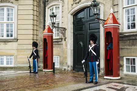 gatehouse: COPENHAGEN, DENMARK - JANUARY 2, 2014: unidentified soldiers of the Royal Guard in Amalienborg Castle guarding the entrance on January 2, 2014 in Copenhagen, Denmark
