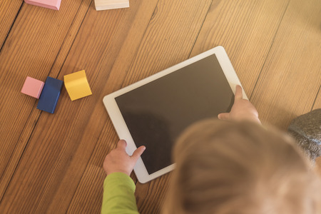 early learning: top view of a toddler playing with a tablet device on a wooden floor with toys in the background