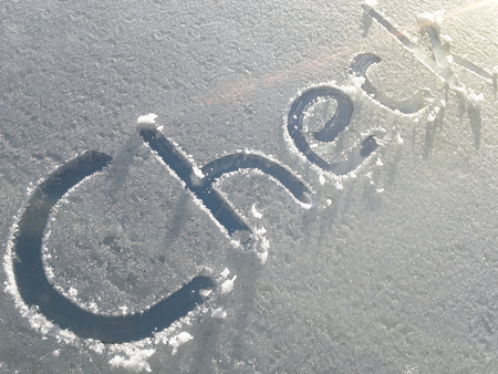 icy conditions: Check drawn on a car windshield covered with fresh snow and ice