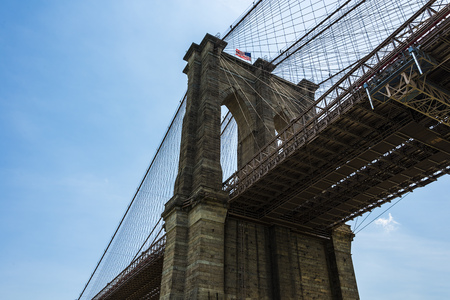 tower of the famous Brooklyn Bridge with american flag on a sunny day, New York City