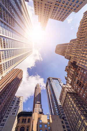 low angle shot of futuristic glass and steel office highrise buildings in the sun, Manhattan financial district, New York City Stock Photo