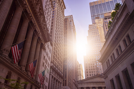 famous New York Financial District with american flags in front of the Stock Exchange Building in the early morning sun, Manhattan financial district