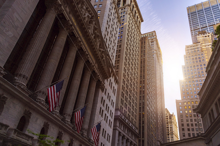 NEW YORK - MAY 17, 2017: famous New York financial district in the early morning sun. American Flags hanging in front of the Stock Exchange Building