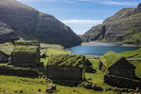 mountain village Saksun with grass roofed houses on the Faroe Islands on a sunny day