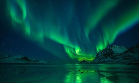 wonderful night sky with aurora borealis over a beach with reflections, lofoten, norway