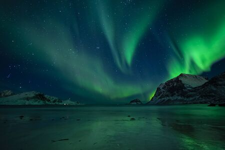 wonderful night sky with northern lights over a beach with reflections, lofoten, norway
