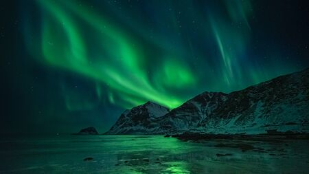 beautiful northern lights over winter sea and mountain scene, lofoten, norway