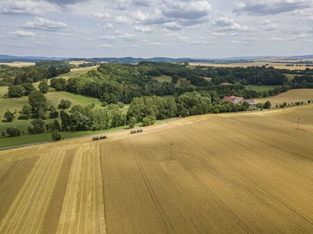 Aerial view of a crops field with forest and hills in the back
