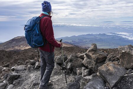 full equipped senior hiker standing on a rocky mountain top with scenic view