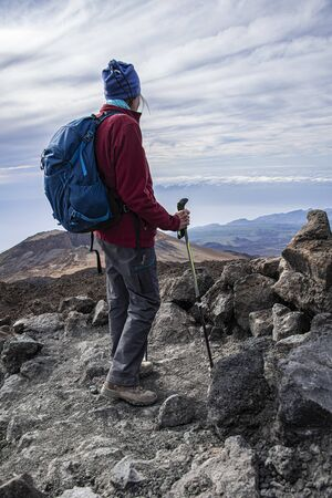 full equipped senior hiker standing on a rocky mountain path with scenic view