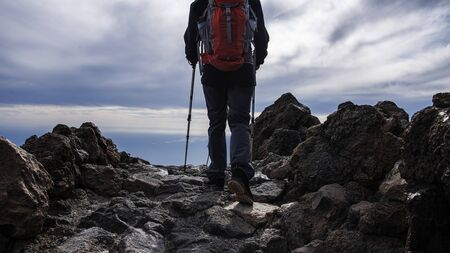 full equipped hiker walking on a rocky mountain path