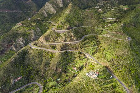 Aerial view of a winding road along a large mountain