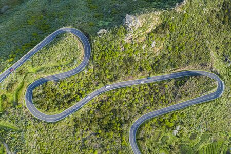 Aerial top view of a winding serpentine road over a a mountain with trees and rocks Reklamní fotografie