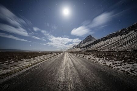 straight country road under the moonlight with dramatic clouds and starry sky, Iceland Reklamní fotografie
