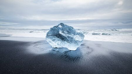 blue ice diamond on black lava sand beach near Jökulsárlón Glacier Lake, Iceland