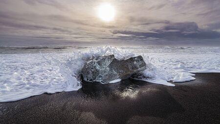 wave crashing on an iceberg on black lava sand beach near Jökulsárlón Glacier Lake, Iceland
