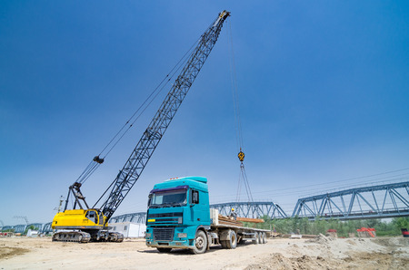 The crane loads the metal structures onto the truck Stock Photo
