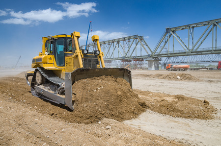 Bulldozer performs excavation work on the background of construction