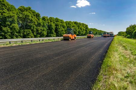 Road roller rolls freshly laid asphalt. Road construction. Stock Photo
