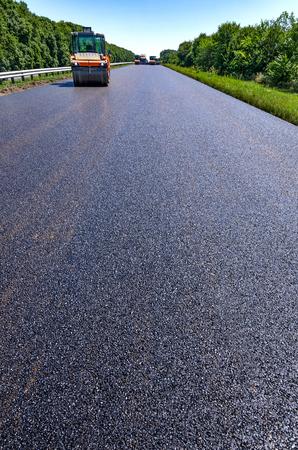 Road roller rolls freshly laid asphalt Stock Photo