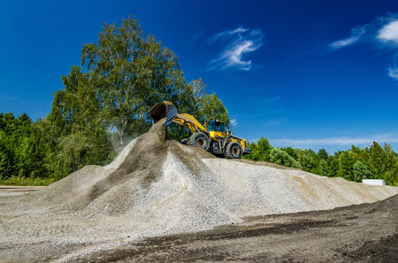 Yellow loader on a hill of crushed stone Stock Photo