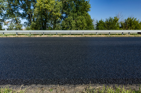 Layer of new asphalt with grass on road construction