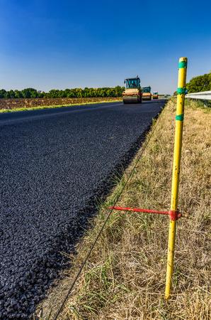 Guide rail. Road roller rolls freshly laid asphalt. Road construction.
