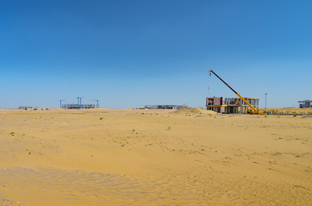 Construction in desert. Yellow crane operation. Banque d'images