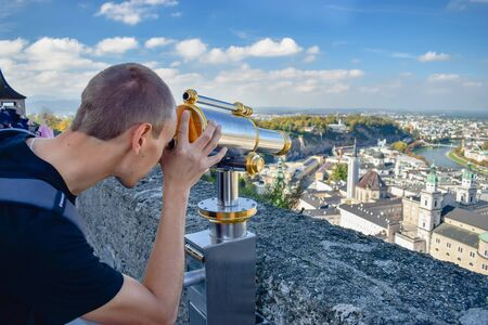 Young man looks by vintage telescope at old city in Salzburg Austria