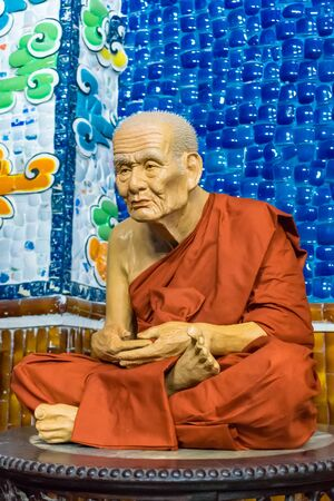 Realistic statue of sitting monk in a red cassock