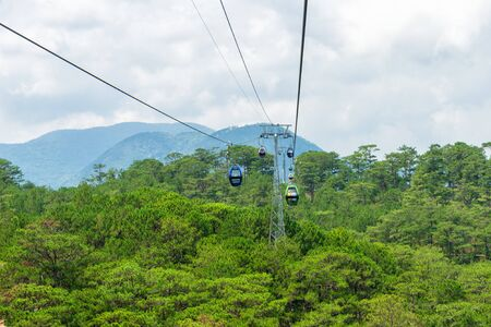 Funicular moves over green tropical forest in mountains in Vietnam